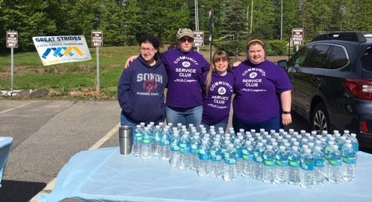 Group of people in front of a table of water bottles